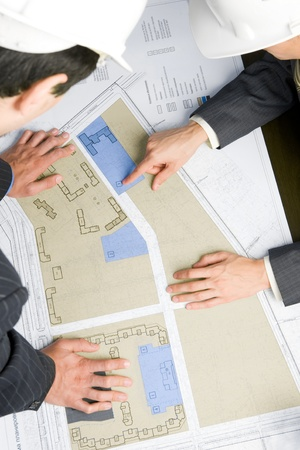Close-up of engineers looking at blueprints with sketches of projects photo