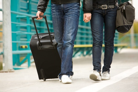Image of couple walking down train station with their baggage photo