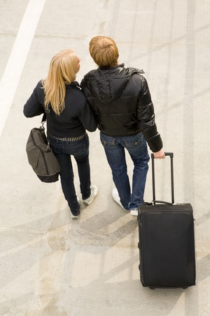 Above view of couple walking down trottoire with their baggage and chatting photo