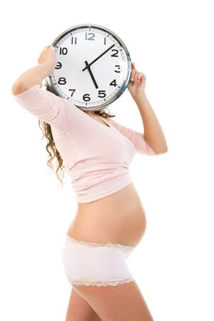 Image of pregnant woman hiding face behind clock over white background photo