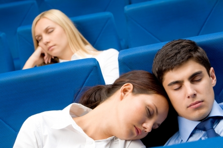Group of business partners dozing in arm-chairs during presentation photo
