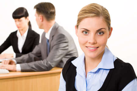 Portrait of happy businesswoman smiling at camera on background of working people photo
