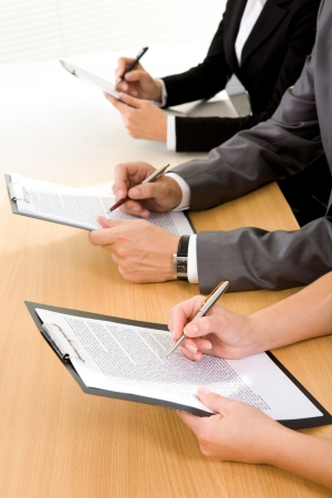 Row of human hands over papers reading business documents photo