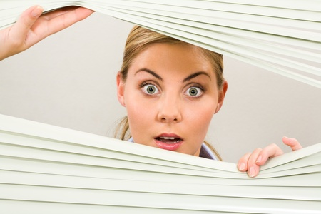 Portrait of surprised woman looking at camera out of venetian blind photo