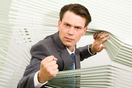 Portrait of angry man looking at camera out of venetian blind and showing fist photo