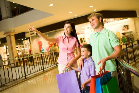 Portrait of pretty female showing something to her husband and son during shopping photo