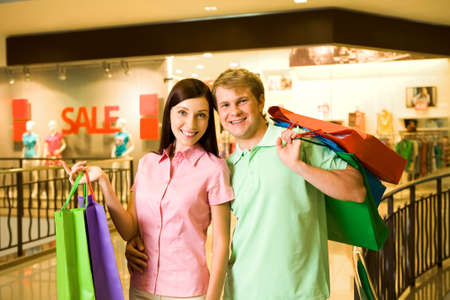 Portrait of shopaholics holding paperbags and smiling at camera Stock Photo - 8507916