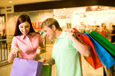 Portrait of pretty female showing bags to happy man after shopping photo