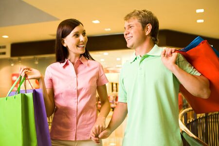 Portrait of pretty female talking to happy man during shopping in trade center photo