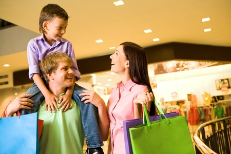 customer relationship: Portrait of joyful woman looking at her son on father's shoulders in the mall