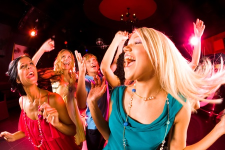 nightclub party: Portrait of cheerful girl dancing at party with her friends on background Stock Photo