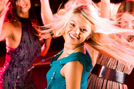 Image of energetic girl looking at camera while dancing on background of her friends Stock Photo - 8507925