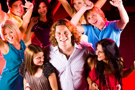 Portrait of happy guy embracing two smart girls in night club at party with their friends behind photo