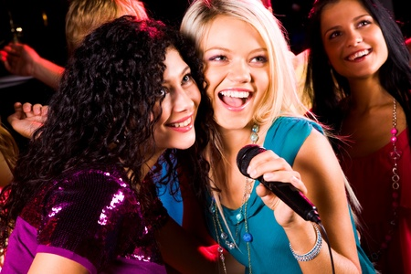 Photo of pretty girls with microphone singing in it photo