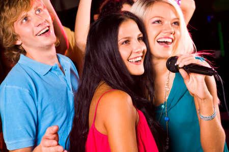 Foto di belle ragazze con microfono per cantare e amichevole ragazzo dietro di loro Archivio Fotografico - 8508323