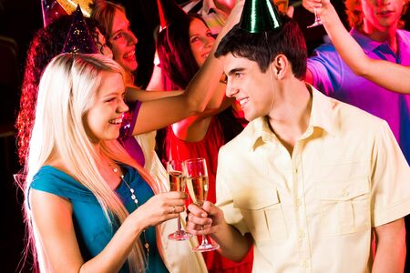 Portrait of happy couple with flutes of champagne with their friends on background photo