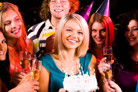 Portrait of joyful girl holding birthday cake surrounded by friends with flutes of champagne photo