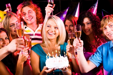 surrounded: Portrait of joyful girl holding birthday cake surrounded by friends with flutes of champagne Stock Photo