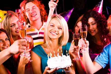 Portrait of joyful girl holding birthday cake surrounded by friends at party photo