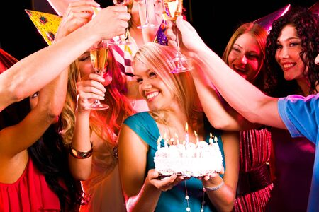 Portrait of joyful girl holding birthday cake surrounded by her friends with flutes photo