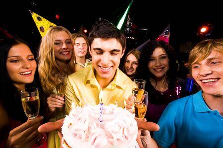 Ritratto di un ragazzo intelligente con torta di compleanno, circondato da amici con champagne