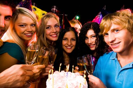 Portrait of smart teens with birthday cake and champagne flutes looking at camera Stock Photo - 8507029