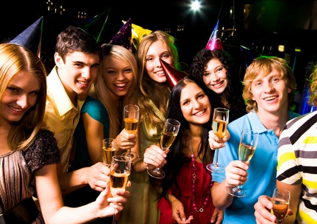 Portrait of glad people in smart clothing with champagne at birthday party photo