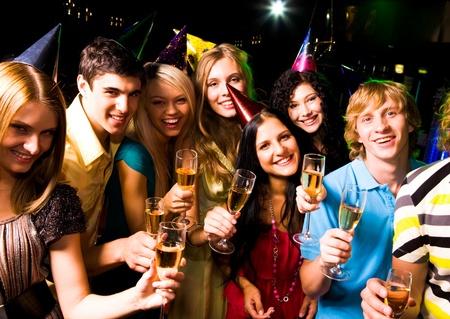 gente celebrando: Retrato de contentos de personas en la ropa inteligente con champ�n en la fiesta de cumplea�os Foto de archivo