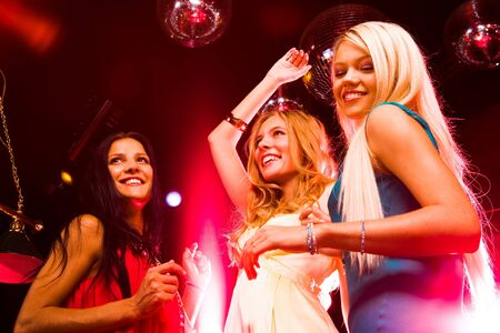 woman night: Three smart dancers moving at disco and having fun