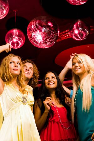 Pretty girls moving at disco with happy guy behind photo