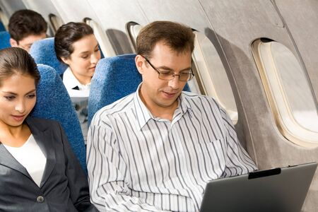 Photo of pretty woman with handsome man typing next to her in airplane photo