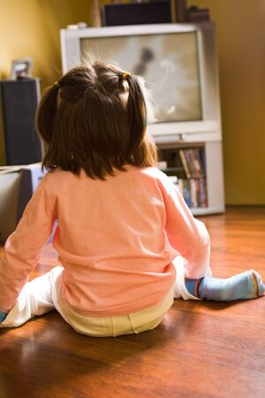 Rear view of little girl sitting on the floor and watching cartoons on TV at home photo