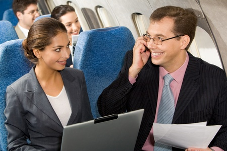Photo of pretty woman communicating with handsome partner sitting next to her in airplane photo