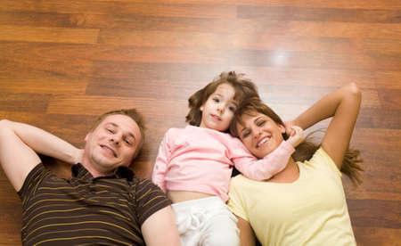 View from above of cheerful family members lying on the floor and looking at camera photo