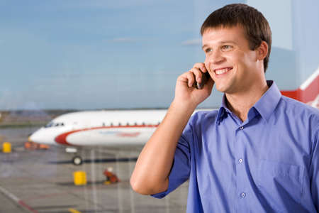 Image of happy male speaking by the mobile phone in airport photo