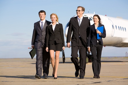 power walking: Group of successful people walking on the background of the airplane