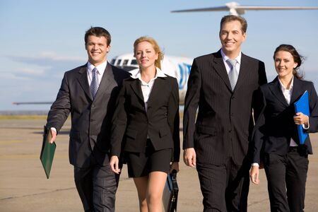 successful leadership: Group of four leaders smiling on the background of the airplane
