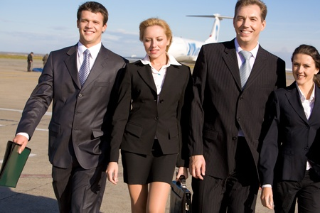 Group of four leaders walking and smiling at camera on the background of airplane photo