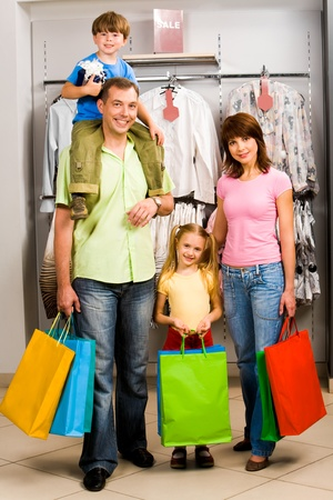 ni�os de compras: Retrato de familia en el departamento de ropa del centro de comercio