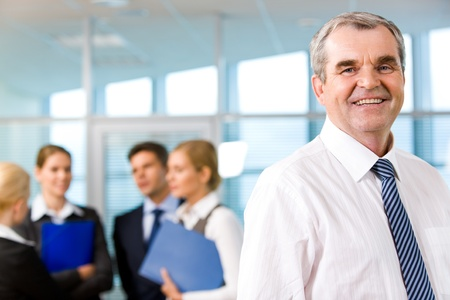 Image of senior leader smiling at camera in working environment photo