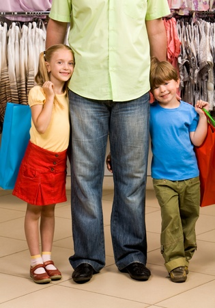 smart girl: Portrait of happy girl and boy embracing their father in the mall