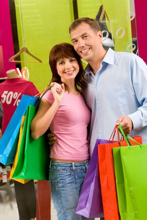 Portrait of shopaholics holding paperbags and smiling at camera Stock Photo - 8507956
