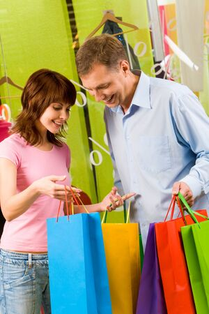 Portrait of pretty female showing bags to happy man after shopping Stock Photo - 8507952