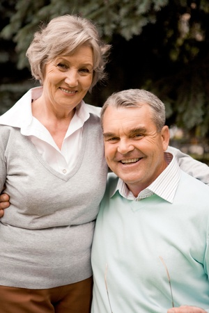 Portrait of senior couple smiling at camera in natural environment photo