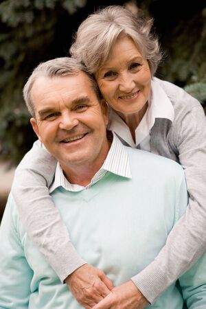 Portrait of senior female embracing her husband while he laughing and both looking at camera Stock Photo - 8508318