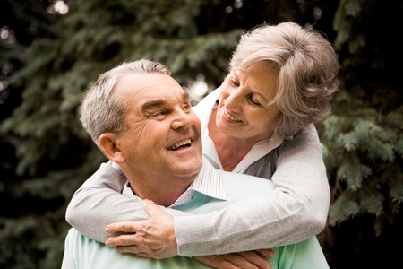 retired: Portrait of senior female embracing her husband while he laughing and looking at her