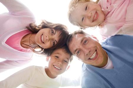 familia unida: Por debajo de la vista de familia mirando la c�mara contra el cielo claro Foto de archivo