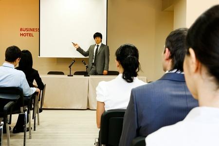 Image of confident businessman explaining something on whiteboard during conference photo
