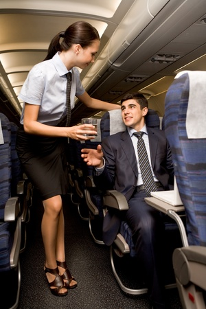 kind: Kind stewardess giving glass of water to young businessman in airplane Stock Photo