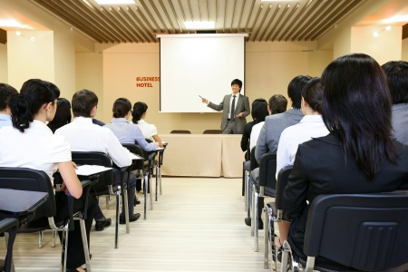 classroom training: Image of confident businessman explaining something on whiteboard during conference